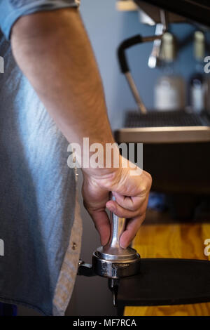 A man presses ground coffee using tamper. Close-up view on hands - Stock Photo