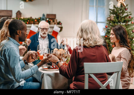family praying before christmas dinner - Stock Photo