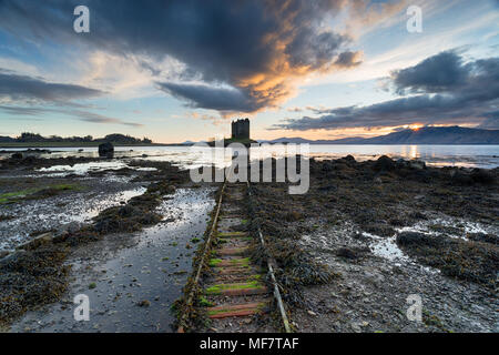Dramatic sunset sky over the ruins of Castle Stalker on the shores of Loch Linnhe near Appin in Argyll in Scotland - Stock Photo