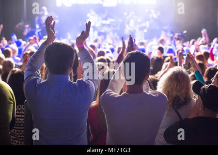 The audience watching the concert on stage in big concert club. - Stock Photo