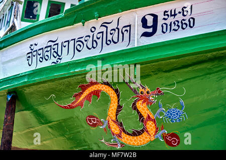 Boat repair and renovation yard with commercial fishing boats adorned with colourful emblems. Thailand, Southeast Asia - Stock Photo