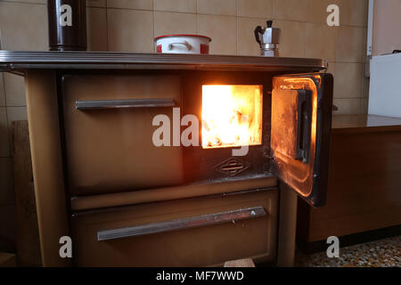 fire of and old stove in the kitchen of a mountain hut - Stock Photo