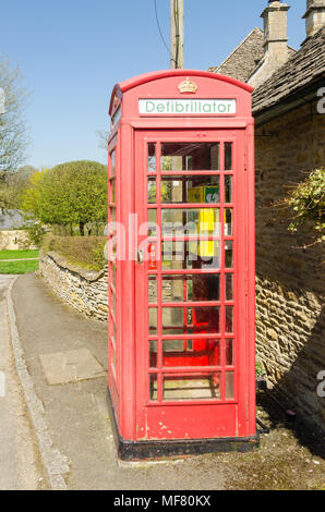 Old red telephone box fitted with a defibrillator in the pretty Cotswold village of Upper Slaughter in Gloucestershire,UK - Stock Photo