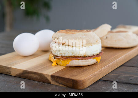 Canadian Bacon, egg and cheese breakfast sandwich with english muffin on cutting board - Stock Photo