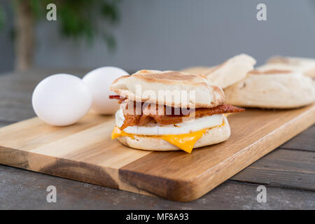 Bacon, egg and cheese breakfast sandwich with english muffin on cutting board - Stock Photo