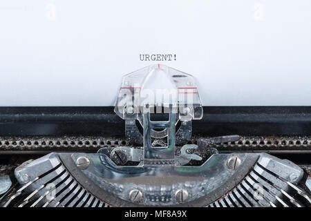 Urgent text typed on an old typewriter - Stock Photo