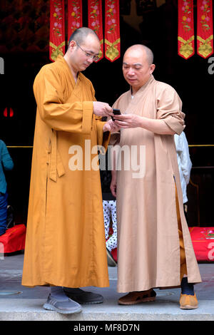 Two Buddhist monks with a mobile phone, Jade Buddha Temple, Shanghai, China - Stock Photo