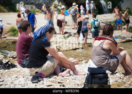 Tourists relaxing by the side of the Neretva River near the Stari Most, Old Bridge in Mostar, Bosnia and Herzegovina - Stock Photo
