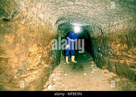Man in underground tunnel works. Employee in safety suit works in medieval tunnel under city. Tunnel built for rich people during wall. - Stock Photo