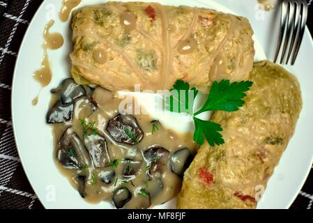 Tasty food, nutrition, kitchen and culinary concept: stuffed cabbage rolls with rice and chicken meat in forest mushroom sauce. - Stock Photo