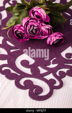 Dinner table with artificial flowers and colorful runners from felt cloth - Stock Photo
