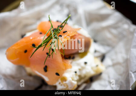 Pretzel with Smoked Salmon, Cream Cheese, Fresh Dill, Black Sesame and Lime - Stock Photo