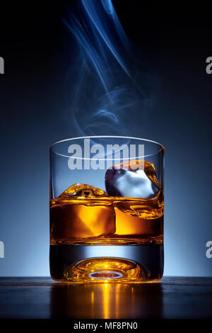Single malt whiskey in a glass with ice on a wooden bar table with cigar smoke on the top of the glass - Stock Photo