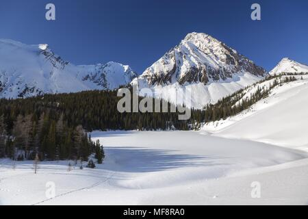 Scenic Winter Landscape View of Frozen Chester Lake and Snowy Peaks in Alberta Kananaskis Country near Banff National Park, Canadian Rocky Mountains - Stock Photo