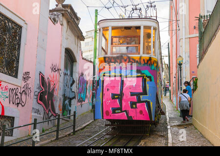 Lisbon Portugal, view of a colorful graffitied tram car descending the Elevador do Gloria in the Baixa area of central Lisbon, Portugal.