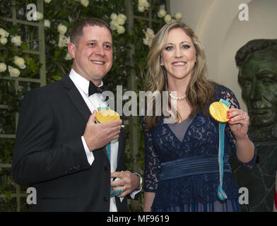 Washington, District of Columbia, USA. 24th Apr, 2018. John Shuster, an American curler who led team USA to gold at the 2018 Winter Olympics, and Meghan Duggan, a three time ice hockey Olympic champion, show off their medals as they arrive for the State Dinner honoring Dinner honoring President Emmanuel Macron of the French Republic and Mrs. Brigitte Macron at the White House in Washington, DC on Tuesday, April 24, 2018.Credit: Ron Sachs/CNP Credit: Ron Sachs/CNP/ZUMA Wire/Alamy Live News - Stock Photo