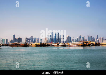 Doha's West Bay skyline with water and dhow boats in the foreground, taken from the port. - Stock Photo