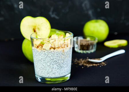 Healthy chia pudding with apples and granola in glass on black background. Vegan creamy breakfast.Detox and healthy superfoods breakfast concept. - Stock Photo