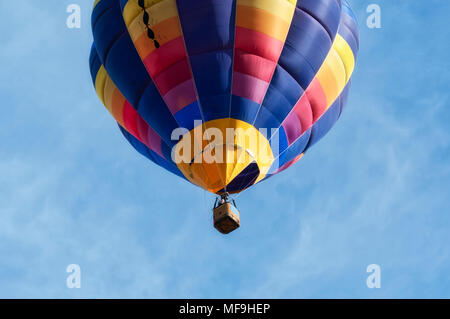 Close-up view from a low angle of a colorful hot-air balloon flying in the clear Italian sky above Udine in daylight. Concept for freedom & adventure - Stock Photo
