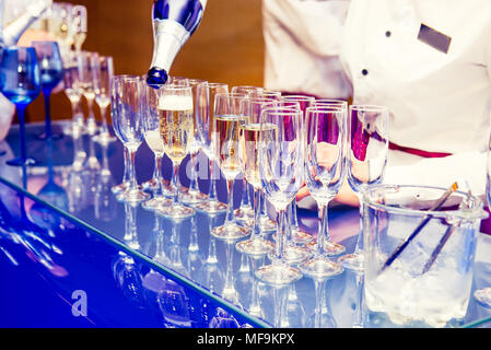 Waiter pouring personal serving Champagne in glasses on bright blue stand. Catering service at events, corporate meeting, party, weddings. Selective f - Stock Photo