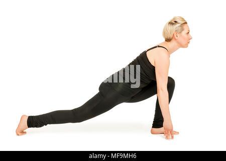 Seitliche Ganzkörper-Ansicht einer jungen Frau vor weißen Hintergrund die Yoga-Übung Ausfallschritt aus dem nach unten gerichteten Hund (adho mukha)