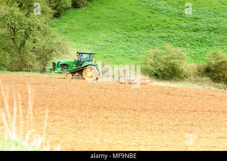 A farmer drives his tractor pulling a harrow over ploughed land on a hillside overlooking the Eyebrook reservoir in England. - Stock Photo