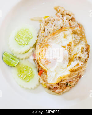 selective focus close up traditional Thai Asian cuisine food menu: delicious Thai fermented pork fried rice with fried egg on top garnished with lemon - Stock Photo