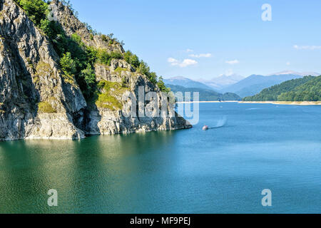Daylight view to Vidraru lake in Carpathian Mountains. Bright blue sky and green trees. Negative copy space, place for text. Transfagarasan, Romania - Stock Photo