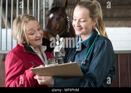 Female Vet Discussing Medical Exam Results With Horse Owner In Stables - Stock Photo
