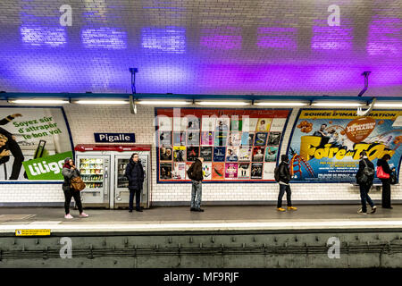 People waiting for a train on Pigalle Metro station which serves lines 2 and 12 of the Paris Métro ,Pigalle, Paris , France - Stock Photo