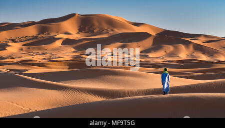 A Berber Man stands at the edge of the Sahara Desert, Erg Chebbi, near Merzouga, Morocco MODEL RELEASED - Stock Photo
