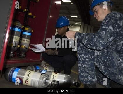 180423-N-OX360-1010 PORTSMOUTH, Va. (April 23, 2018) Airman Devan Beatie, from Salt Lake City, left, and Aviation Boatswain's Mate (Handling) 3rd Class Kelii Denny, from Virginia Beach, Va. conduct maintenance on a self-contained breathing apparatus (SCBA) aboard the aircraft carrier USS Dwight D. Eisenhower (CVN 69)(Ike), April 23, 2018. Ike is undergoing a Planned Incremental Availability (PIA) at Norfolk Naval Shipyard during the maintenance phase of the Optimized Fleet Response Plan (OFRP). (U.S. Navy photo by Mass Communication Specialist Seaman James Norket). () - Stock Photo
