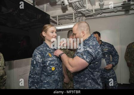 180423-N-LA456-0013 PORTSMOUTH, Va. (April 23, 2018) Master-At-Arms 1st Class Nancy Freeman receives her enlisted surface warfare specialist pin in the Five-Star classroom of the aircraft carrier USS Dwight D. Eisenhower (CVN 69) (Ike), April 23, 2018. Ike is undergoing a Planned Incremental Availability (PIA) at Norfolk Naval Shipyard during the maintenance phase of the Optimized Fleet Response Plan (OFRP). (U.S. Navy photo by Mass Communication Specialist Seaman Ashley M.C. Estrella). () - Stock Photo
