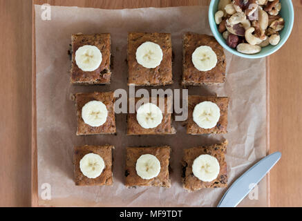 Slices of freshly baked banana bread, displayed on a wooden board.  This healthy snack is gluten and dairy free - and delicious! - Stock Photo