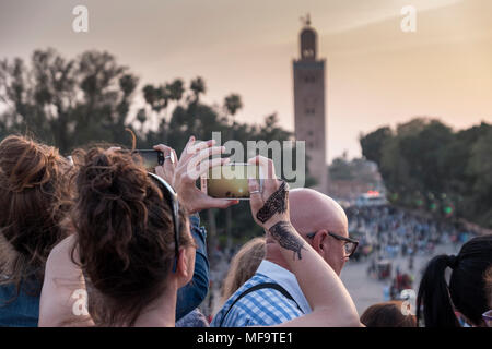 A Woman with Henna Tattoos on ther hands photographs the Koutoubia Mosque on her iphone at sunset, Marrakech, Morocco - Stock Photo