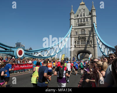 View of runners in the 2018 London Marathon crossing Tower Bridge - Stock Photo
