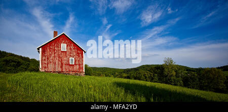 Classic antique red Vermont barn in the beautiful meadow on a summer day - Stock Photo
