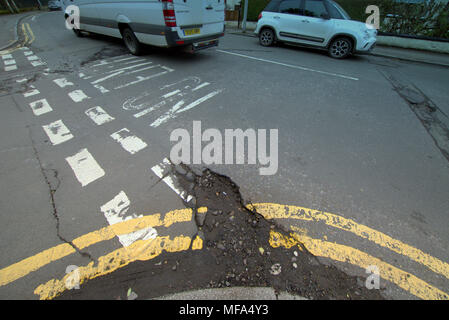 pot holes damaged road  car cars on street with  double yellow lines no entry markings - Stock Photo