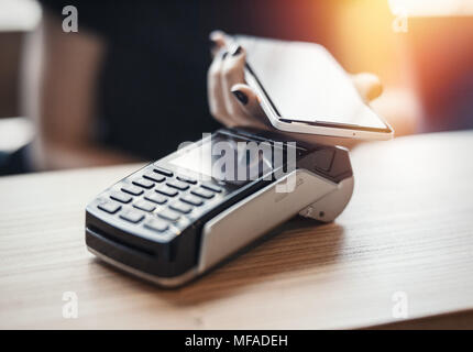 Young woman pays via payment terminal and mobile phone. - Stock Photo
