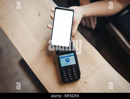 Young woman pays via payment terminal and mobile phone in cafe. - Stock Photo