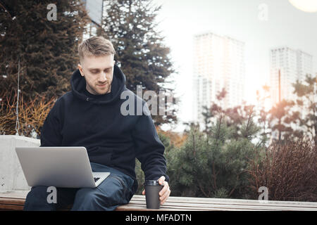 Young man holding laptop on knees. Black coffee cup is next to him. - Stock Photo