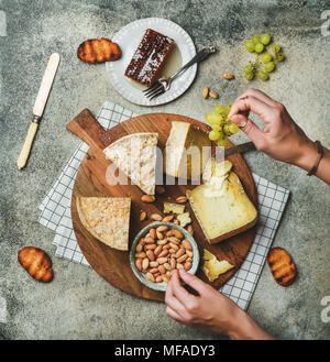 Cheese platter with female hands reaching to food - Stock Photo