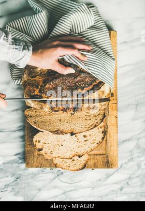 Female hands cutting freshly baked sourdough bread, vertical composition - Stock Photo