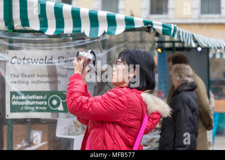 Oriental lady in a red coat taking a photograph in the market place of Cirencester, Gloucestershire, England, UK - Stock Photo