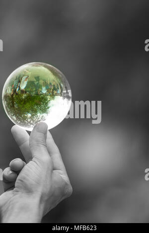 black and white image of hand holding green glass crystal ball between thumb and forefinger - Stock Photo