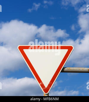 road sign of priority, requiring drivers to give way to vehicles moving along a crossed road against a blue sky with clouds - Stock Photo