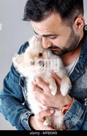 man holds pomeranian dog - Stock Photo