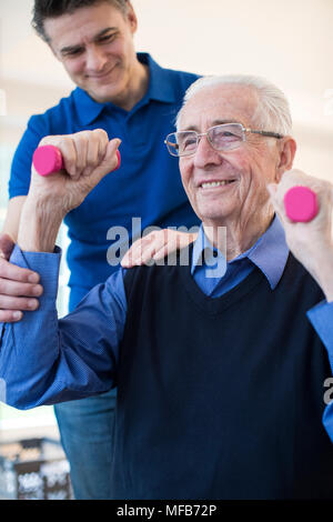Physiotherapist Helping Senior Man To Lift Hand Weights - Stock Photo