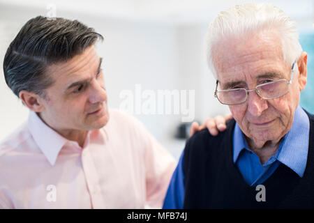 Confused Senior Man With Adult Son At Home - Stock Photo