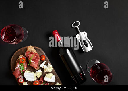 Prosciutto, salami, baguette slices, tomatoes and nutson rustic wooden board, two glasses of red wine over black background - Stock Photo